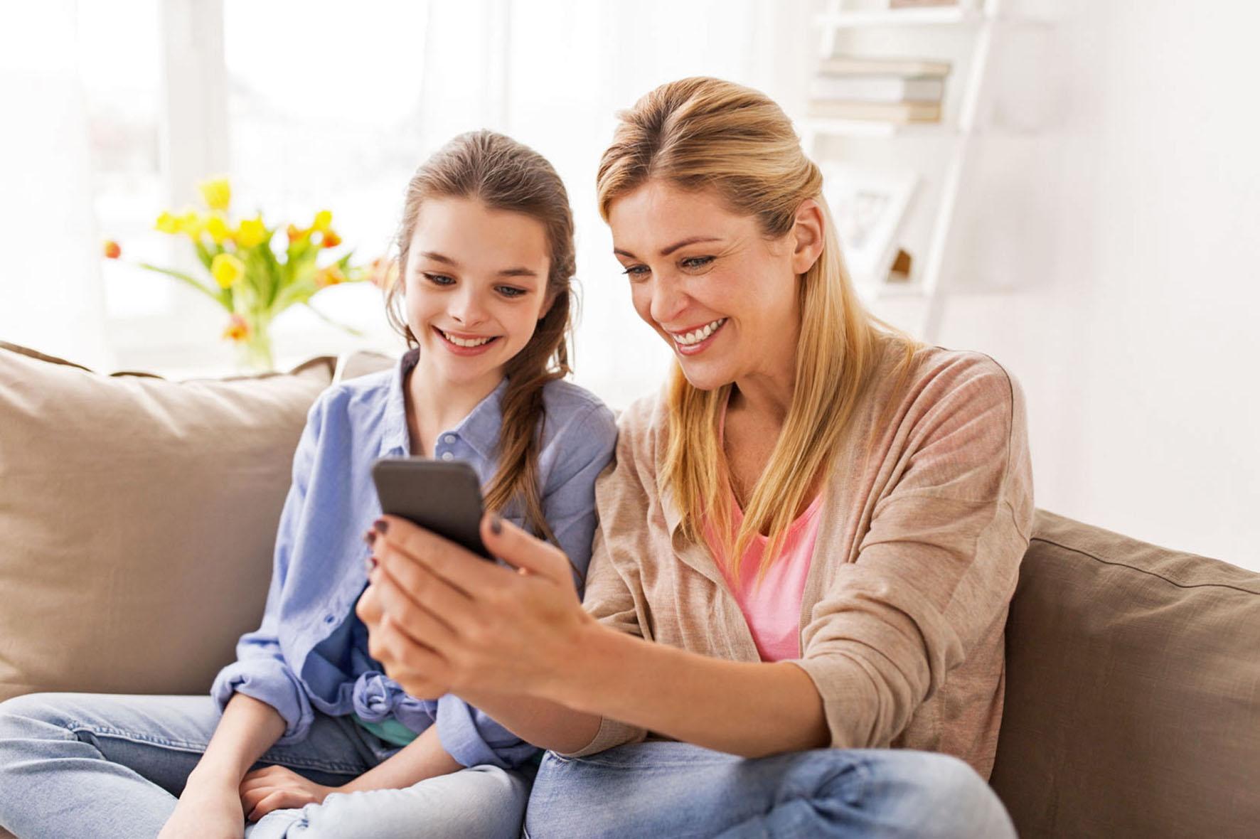 Mutter und Tochter am Handy - Das Kind hat Diabetes