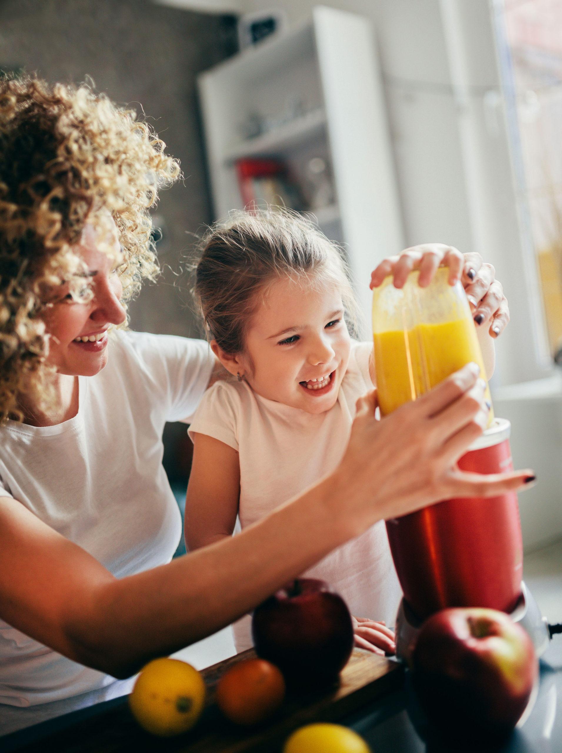 Mutter und Tochter beim Smoothies selbst machen