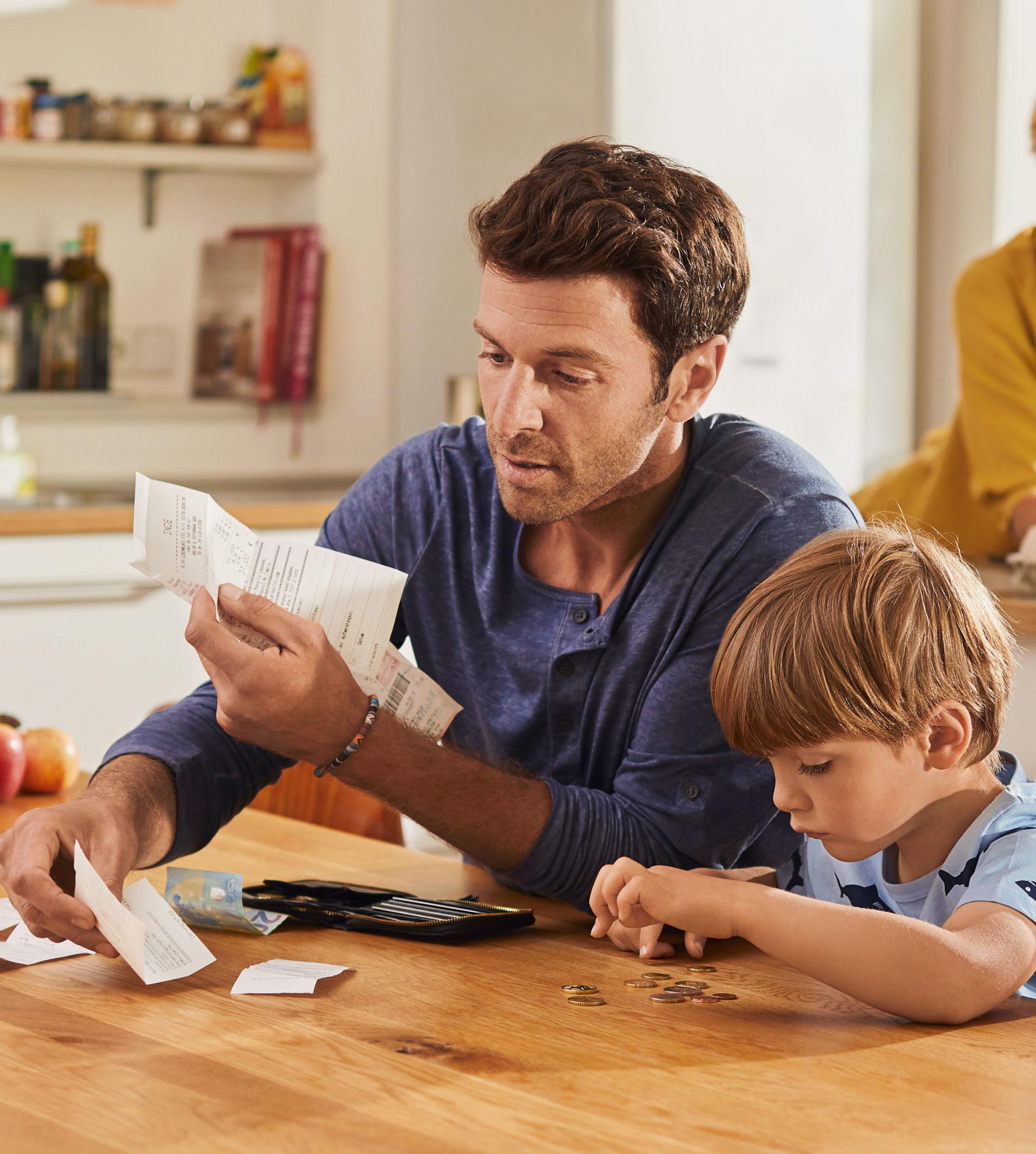 Vater und Sohn beim Geld zählen - Als Familie sparen